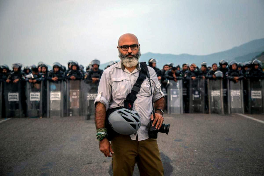 2019 Award winning Pulitzer Prize Breaking News photographer Adrees Latif, 1991 JVHS alumnus, stands before Mexico's Federal Police near the state line of Oaxaca and Chiapas. Latif covered the migrant caravan last year, which the police temporarily halted.