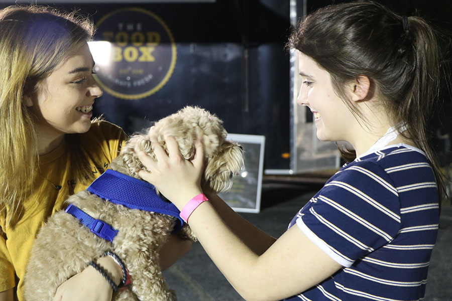 """Accompanied by her friend Kimberely Vinson, Cianni Sellers, senior, plays with the girl's dog """"I would tell someone to expect lots of families and a variety of food options to choose from. Live music and entertainment for the kiddos like a bounce house were available,"""" Vinson  said,"""