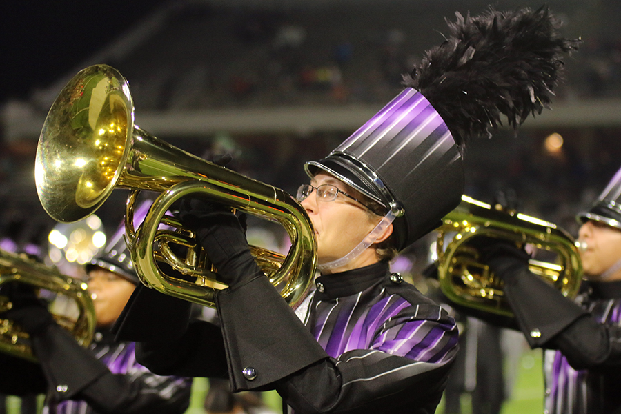 """During the halftime performance of the game versus Cy Falls,  Cole Stachowiak, junior, accompanies his section playing """"46 and Broadway"""". """"I enjoyed the games and practices because we all were sharing the same hardships and successes as a group,"""" Stachowiak said."""