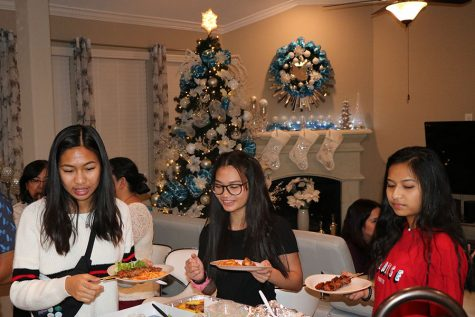 After expressing their gratitude for their meal and gathering through prayers, Filipino friends and family line up to take their share of what has been prepared. Conversations and warmth fill the festive atmosphere.
